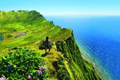 Wanderin genießt Aussicht von Vulkankrater über das Meer auf den Azoren