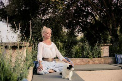 Frau bei Yoga und Meditation im Garten mit Katze auf Mallorca Finca moit Neue Wege Reisen