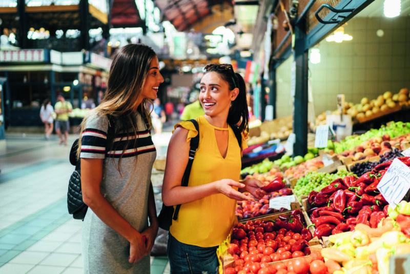 Zwei Frauen sprechen miteinander am Gemüsestand auf einem Markt auf Reisen